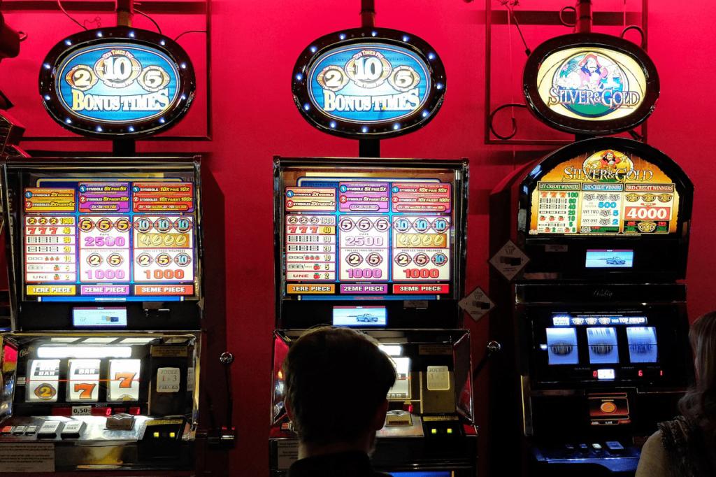 Mann steht vor drei Spielautomaten vor roter Wand